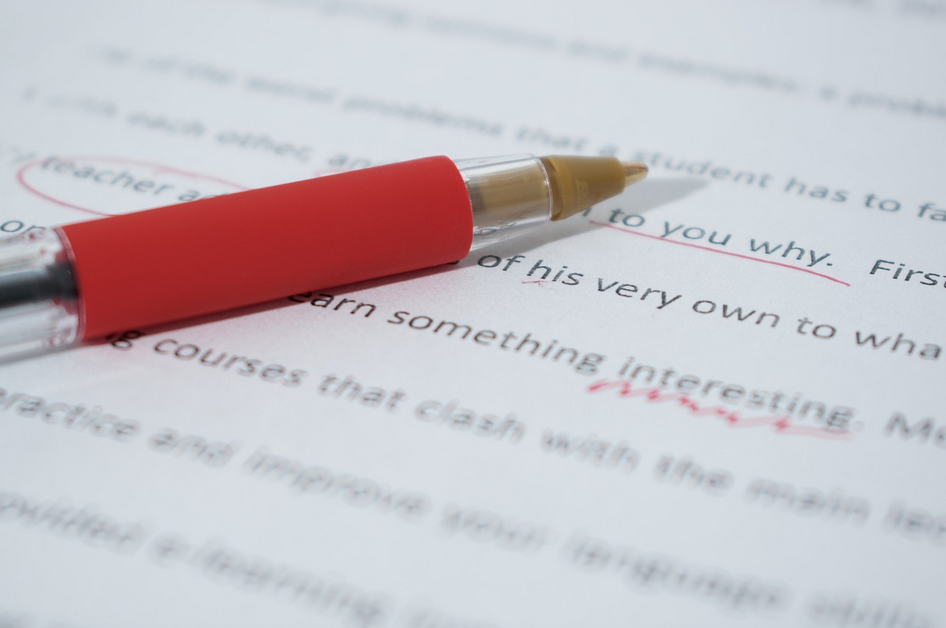 photo of a red pen lying on a paper with written edits