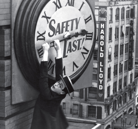 Photo of Harold Lloyd hanging from a clock face in the silent film Safety Last