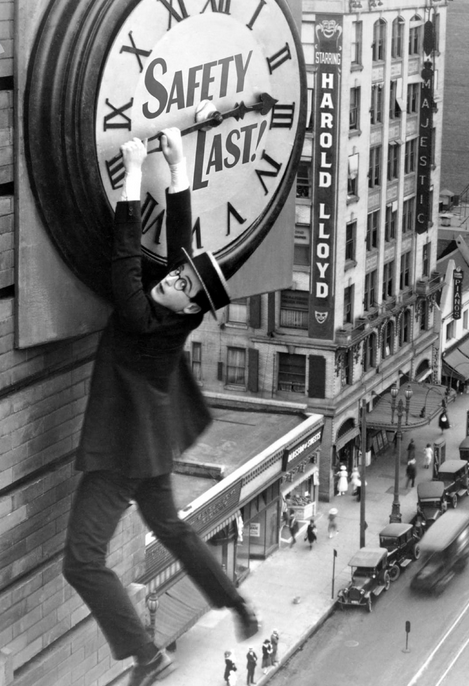 Image of Harold Lloyd clinging to hands of a clock on side of building.