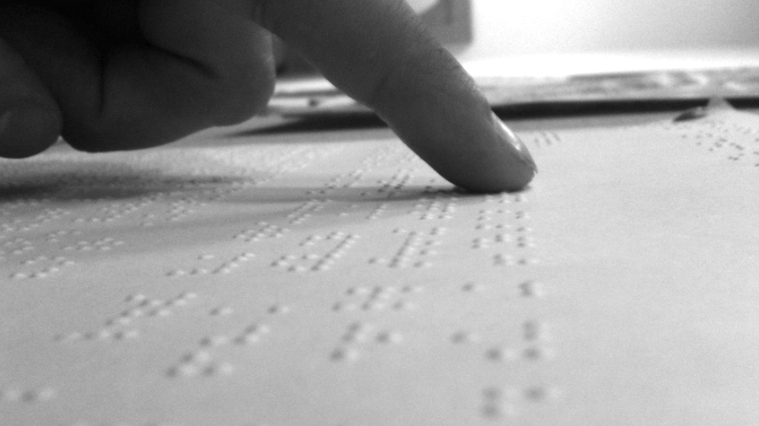 black and white photo of a person's finger reading Braille