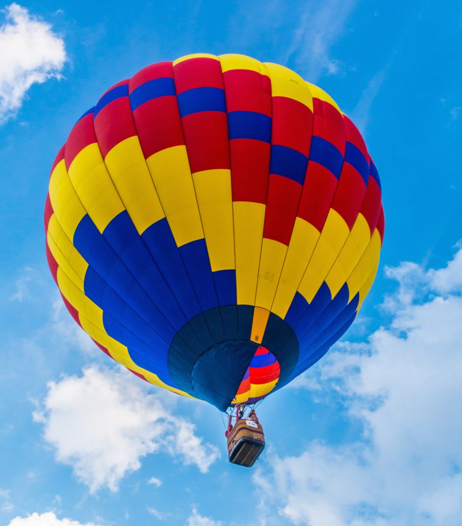 photo of a red, yellow, and blue hot air balloon against a blue sky